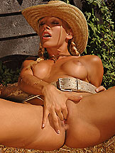 Blonde cowgirl Sandy stuffing a bottle at the farm