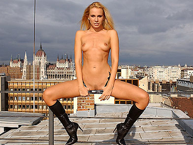 Exhibitionist Sandy dildoing her holes on balcony