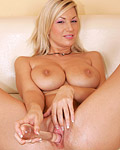 Busty blonde Carol puts a big glass toy inside her pussy