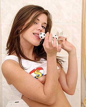 A cute washing teenager masturbates with two small balls