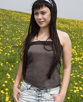 Hot teenage chick pleasures herself on a big grass field