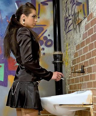 A teenage brunette jizzed by a fake cock in public toilet