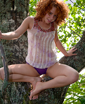 A pretty deranged teenage redhead hanging out in a tree
