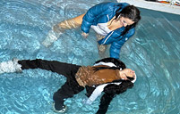 Sexy clothed lesbian sweeties swimming in a public pool