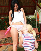 Two lesbian beauties massaging their wet cunts outdoors