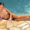Teen hottie in bikini strips and fucks vibrator in the pool