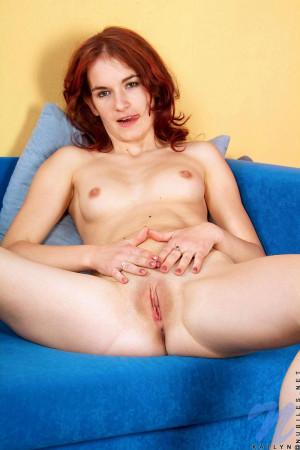 Bare skinned redhead katlyn posing her fair slender body on the sofa