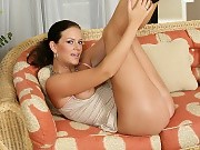 Tempting brunette plugs pussy and ass with sex toys on couch