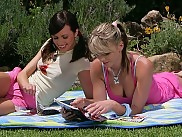Teen beauties make sweet love on a blanket in the garden