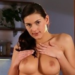 Busty brunette strips and spreads pink twat in the kitchen