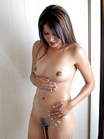 Slender brunette strips showers and rubs wet hairy pussy