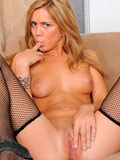 Seductive nymph in fishnet stockings finger fucks her cock craving pussy