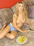 Tasty bosomy babe with grapes posing nude in sofa