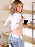 Blonde haired Nubile Jilova exposes her enticing tits and ample ass on the red couch